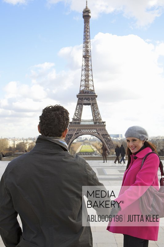 Couple holding hands in front of the Eiffel Tower