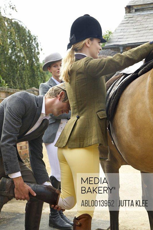 Man Helping Woman Mounting Horse