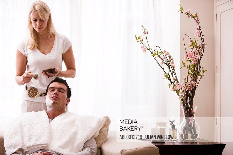 Woman applying shaving cream on man face