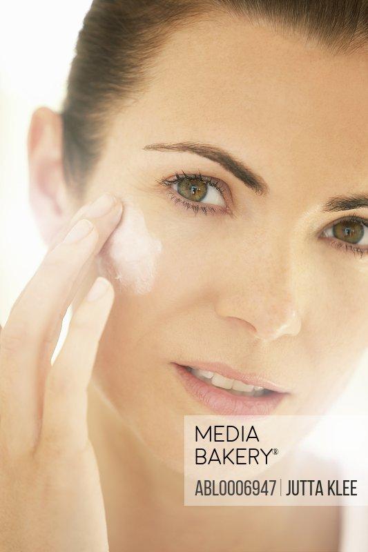 Woman Applying Moisturizing Cream on Face, Close-up view