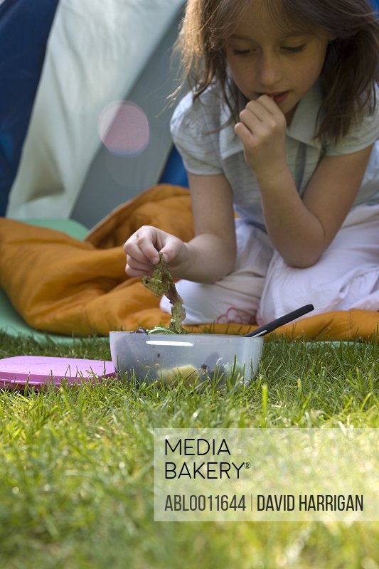 Young girl kneeling by tent entrance eating salad