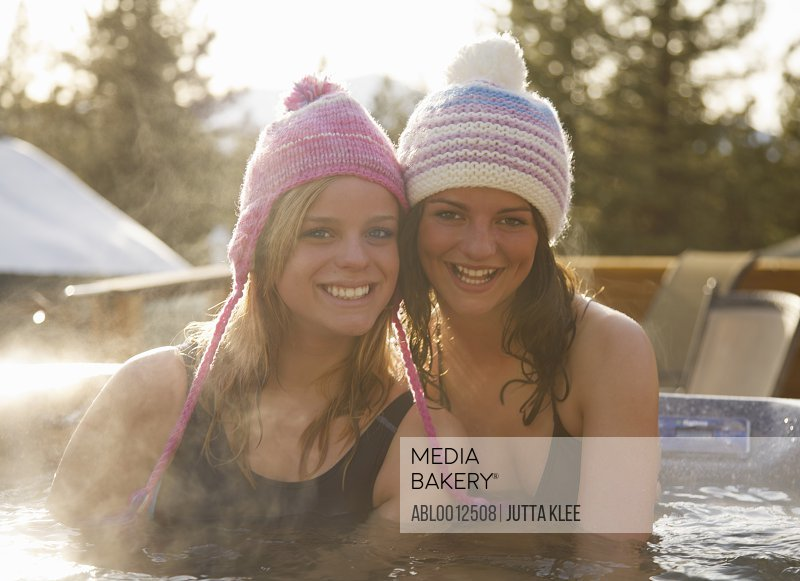 Two smiling young women relaxing in a hot tub après-ski
