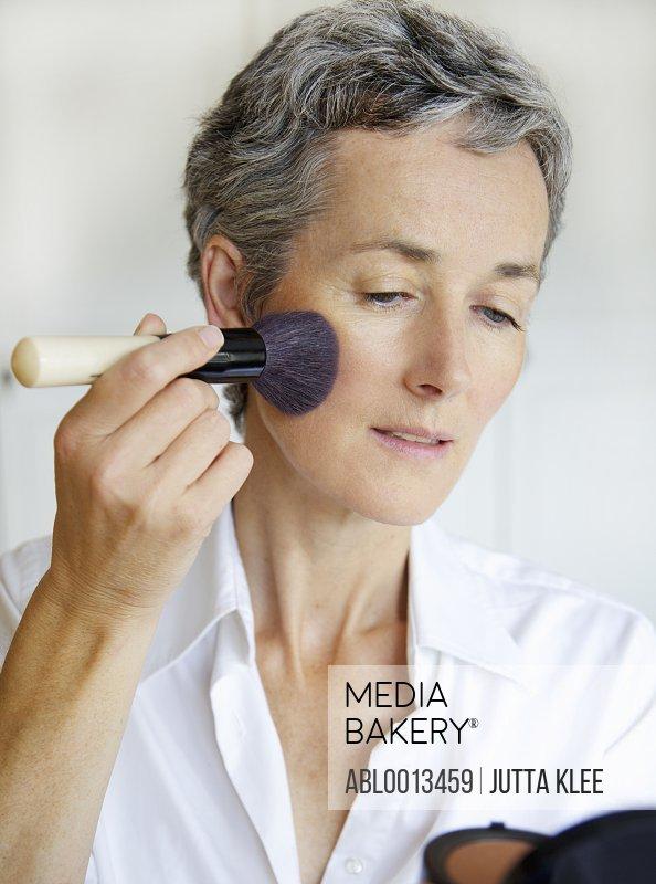 Woman Holding Compact Mirror Applying Blush