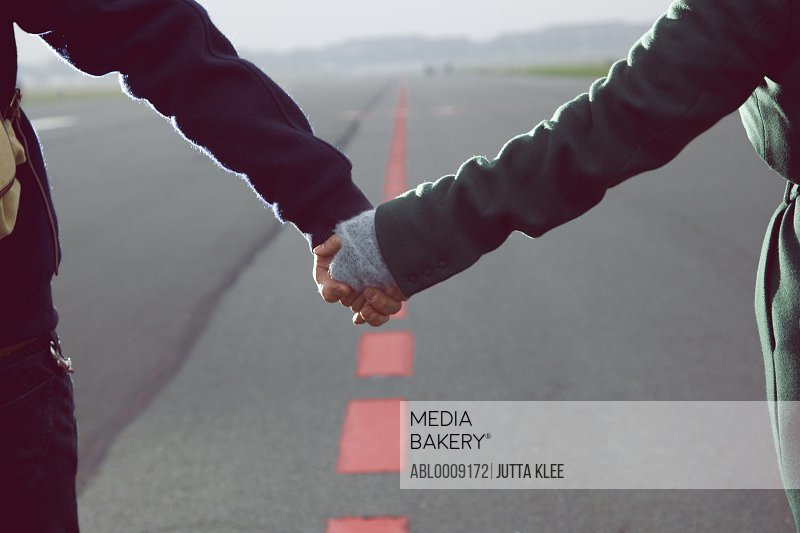 Couple Holding Hands on Airport Runway, Close-up view