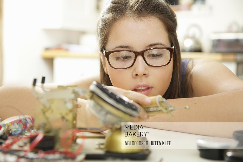 Teenage Girl Building a Telephone for Engineering School Project