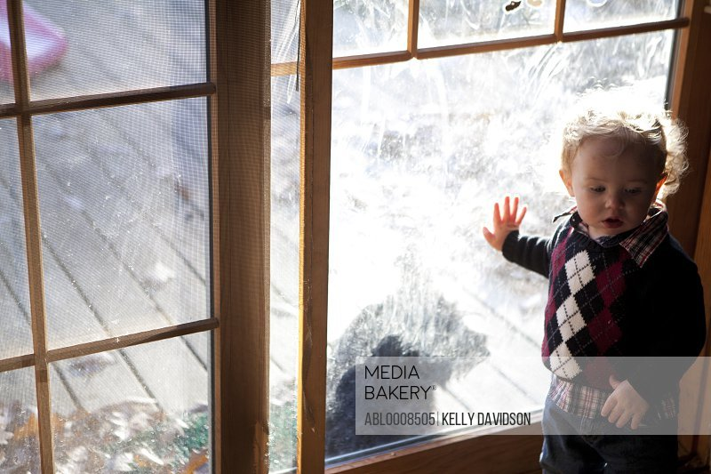 Young Boy Standing by Dirty Window