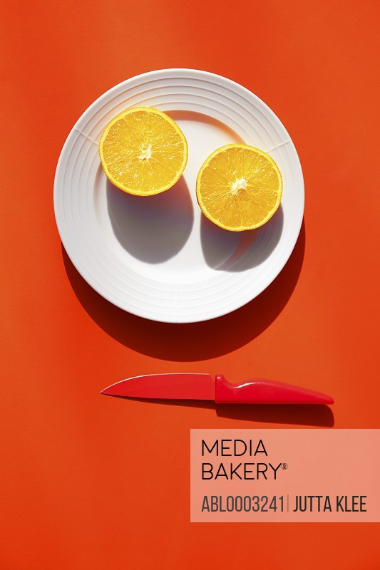 Halved Orange on Plate with Knife