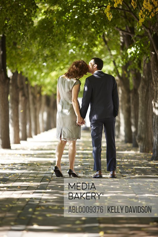 Couple Walking on Tree Lined Street Holding Hands, Back View