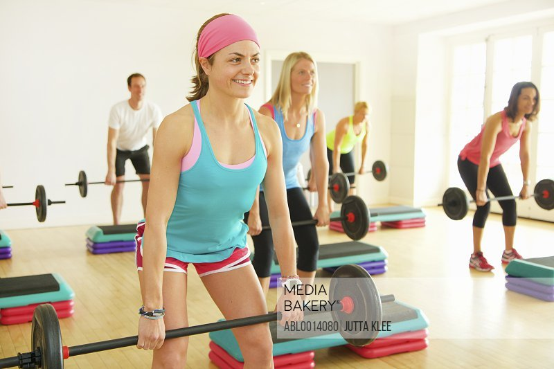 Group of People Lifting Barbells at Fitness Class