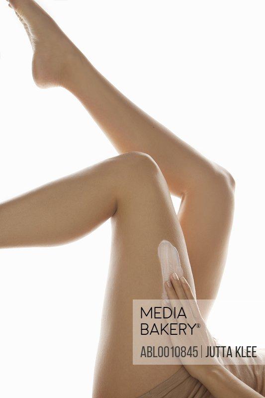 Woman Applying Body Lotion on Legs