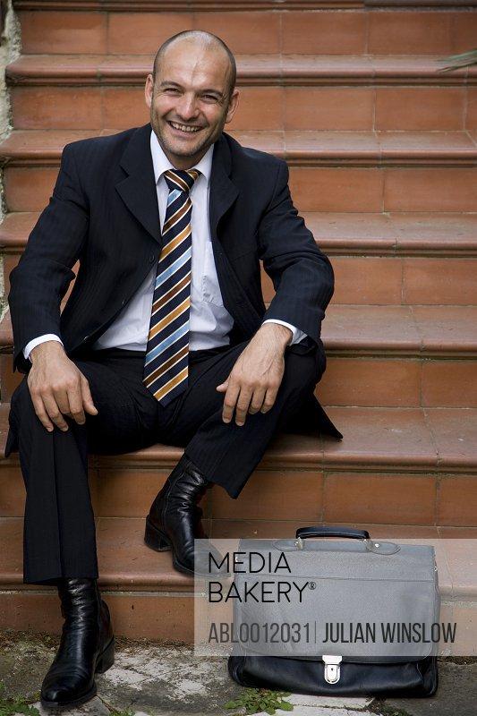 Businessman sitting on steps smiling