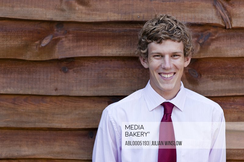Young businessman standing against a wood wall