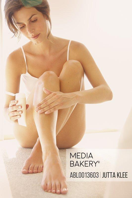 Woman Applying Body Lotion on Leg