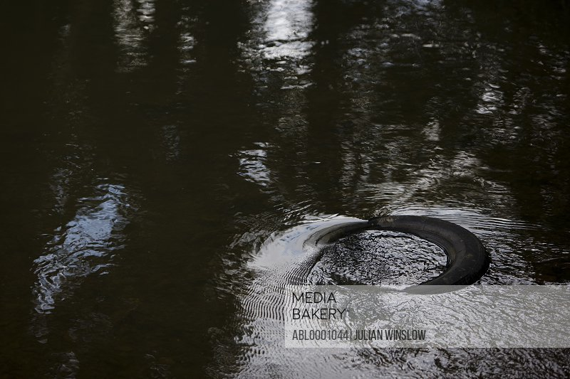 Close up of a discarded rubber tyre floating in a river