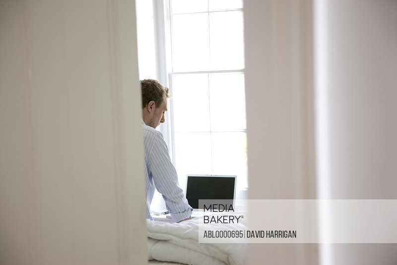Man sitting on bed looking at laptop computer