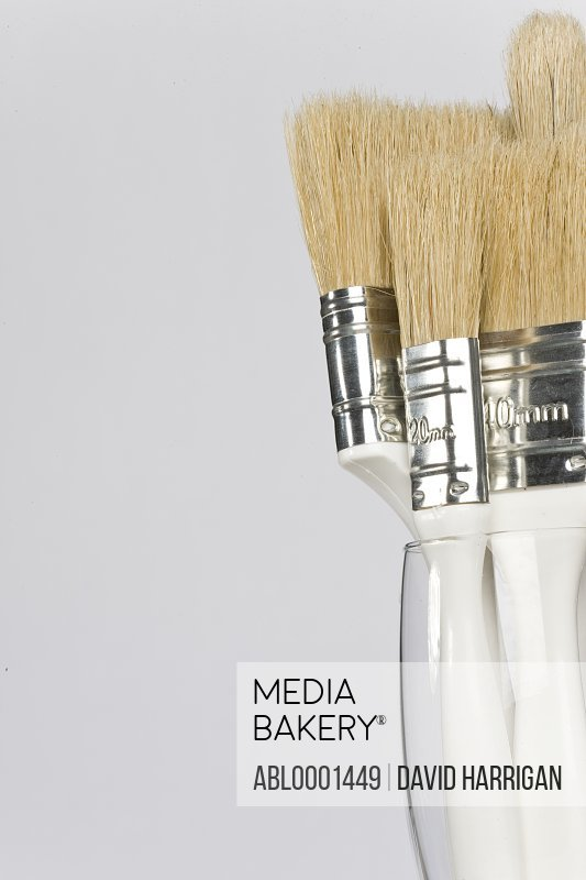 Close up of white paintbrushes set in a glass