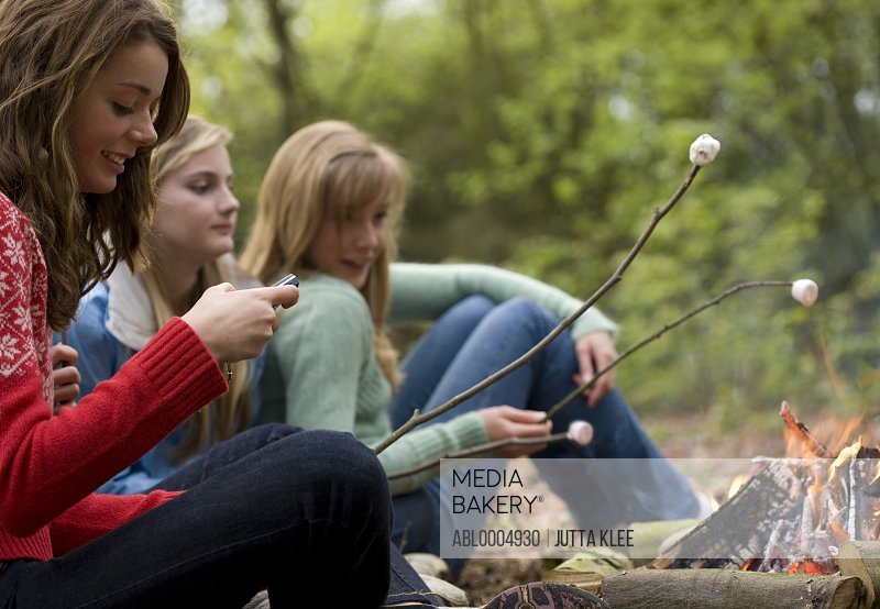 Teenage girls roasting marshmallow over campfire