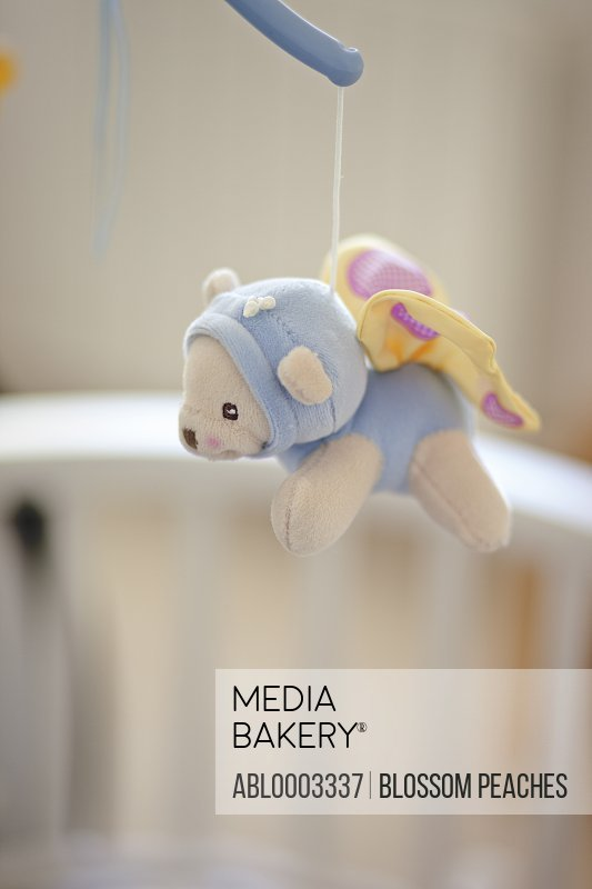 Stuffed Animal Hanging from Mobile over Baby Crib