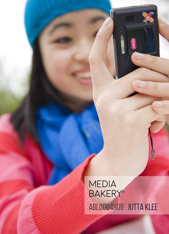Close up of teenaged girl hands taking self-portrait with camera