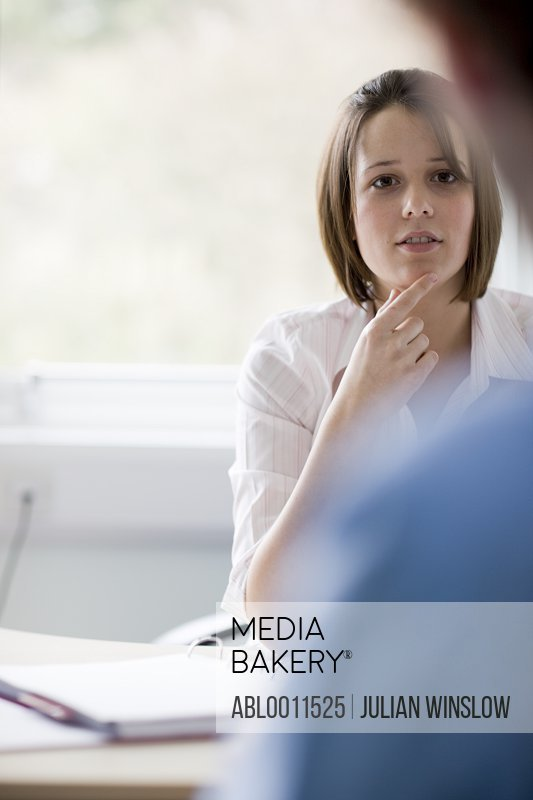 Portrait of young businesswoman talking to colleague