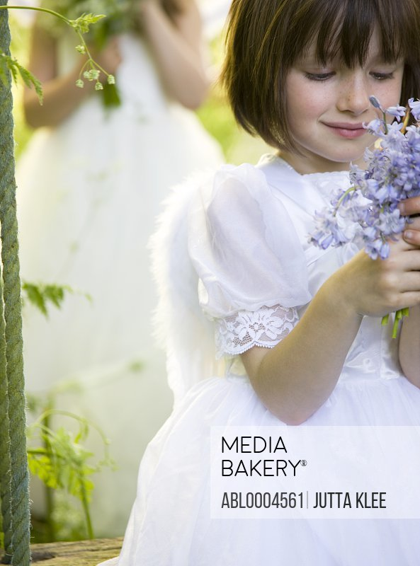 Portrait of a girl in a fairy costume holding flowers
