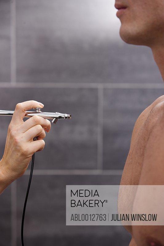 Profile a man getting a fake tan with an airbrush gun