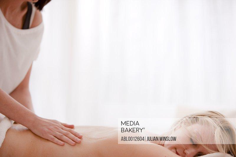 Masseuse giving a woman a back massage