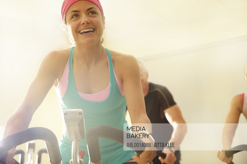 Woman Using Exercise Bicycle at Fitness Class