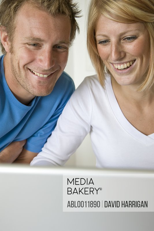 Close up of a couple laughing and looking at laptop computer screen