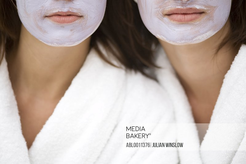 Close up of two young women with mauve beauty mask and white bathrobes