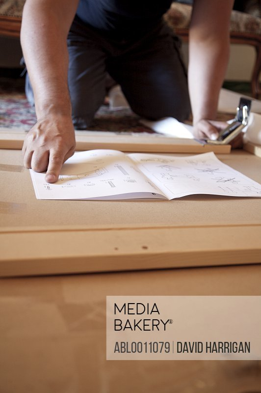 Man's hands on flat pack furniture instructions