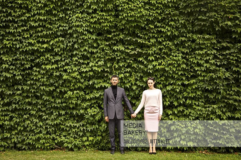 Couple Holding Hands Standing in front of Green Leafy Hedge