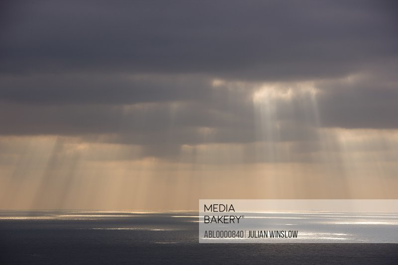 Grey sky with sun rays shining on the ocean