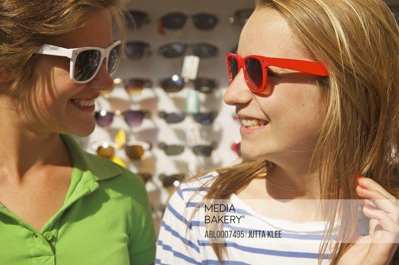 Smiling Teenage Girls Shopping for Sunglasses