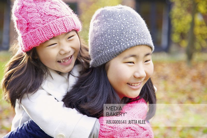 Two Young Girls Riding Piggyback Outdoors