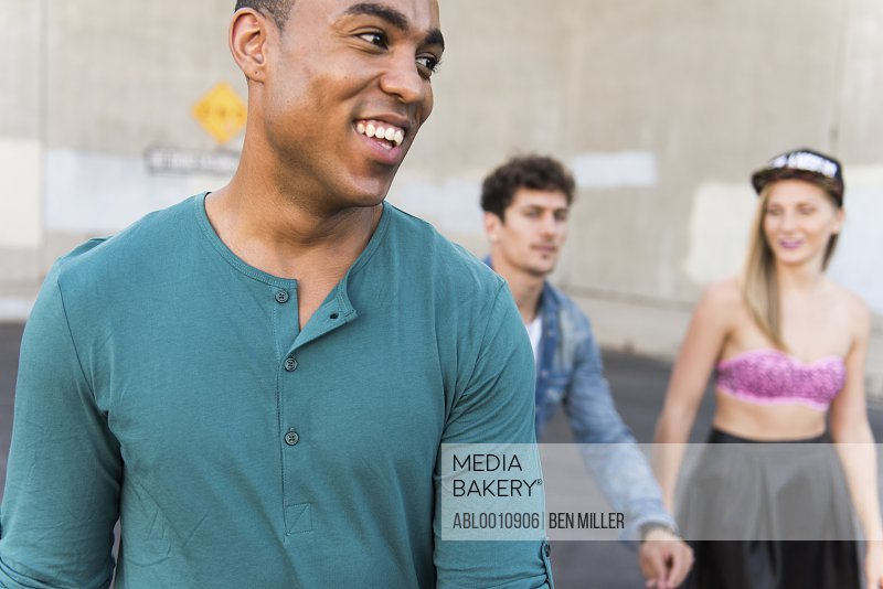 Man Walking on Street with Friends Smiling