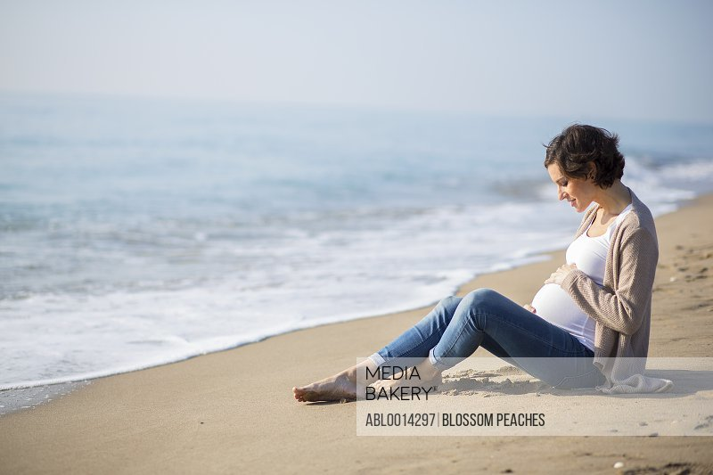 Pregnant Woman Sitting on Beach Touching her Belly