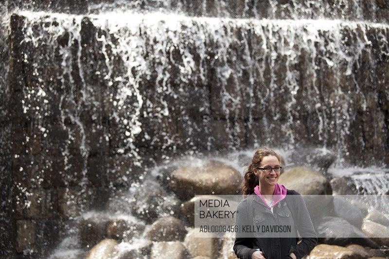 Woman Standing in front of Shinjuku Chuo Park Waterfall, Tokyo, Japan