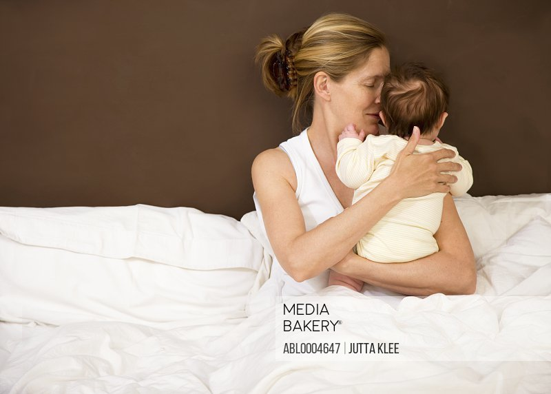 Portrait of a woman in bed with her newborn baby