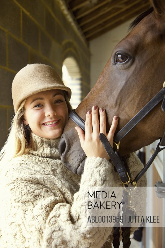 Smiling Young Woman Stroking Horse Head