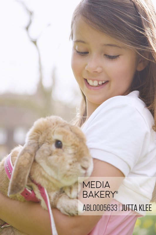 Young girl holding a lop-eared rabbit