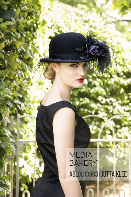 Young Woman Wearing Bowler Hat with Feathers Outdoors