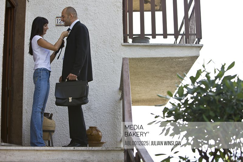 Businessman leaving for work with woman adjusting his tie