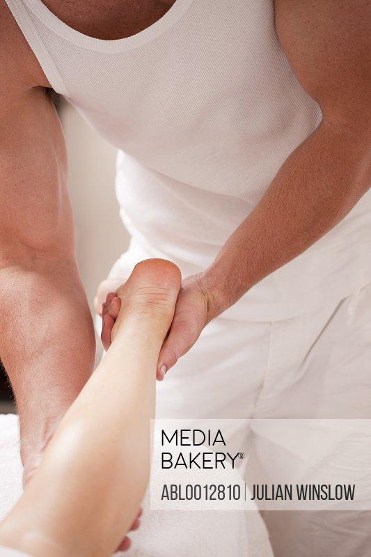 Close up of a masseur massaging a woman leg