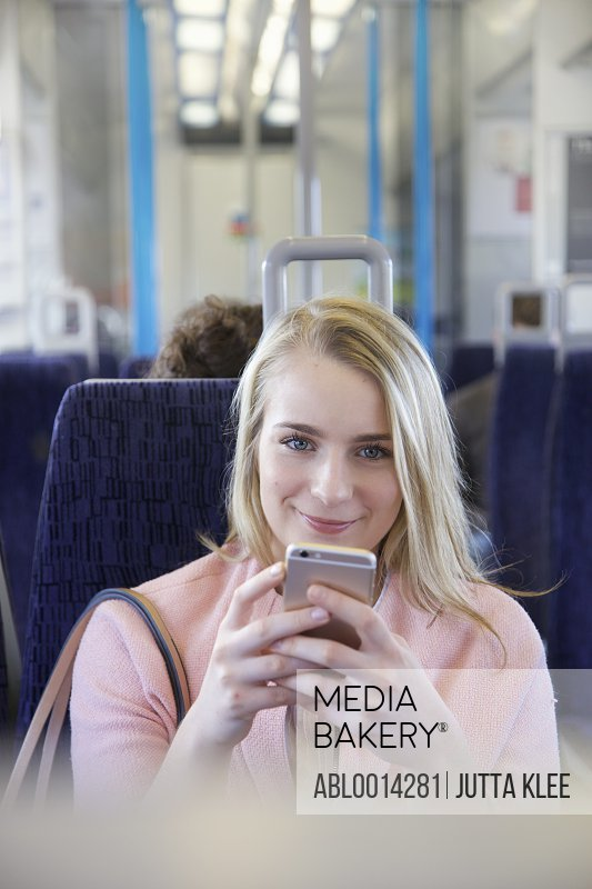 Young Woman Using Smartphone on Commuter Train