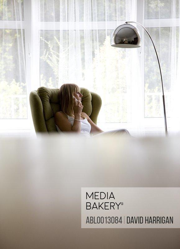 Woman Sitting by Window Using Telephone