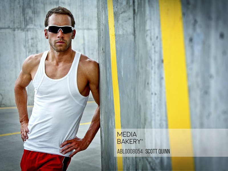 Sportsman Leaning against Concrete Wall