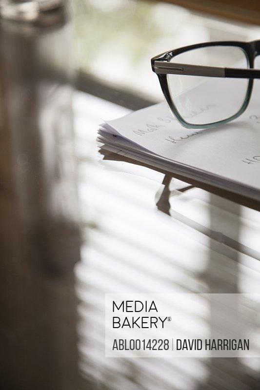 Eyeglasses and Paperwork on Desk