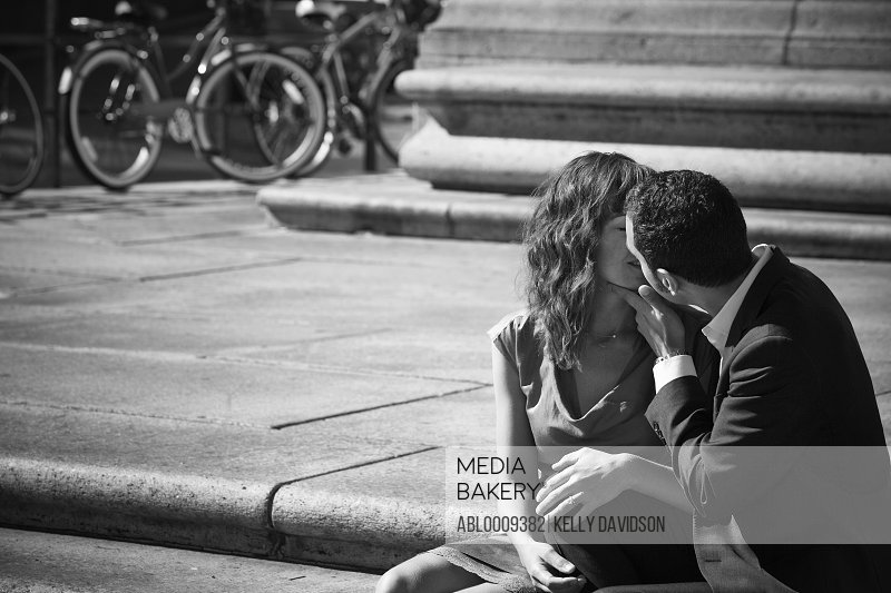Couple Kissing on Steps in Public Square