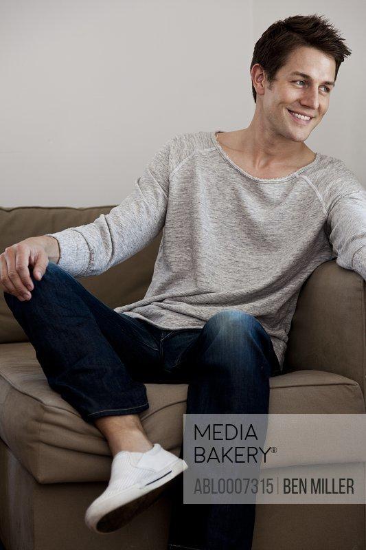 Smiling Man Sitting on Sofa